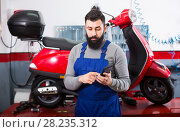Купить «Beardy guy is preparing bill for motorcycle repair», фото № 28235312, снято 25 мая 2018 г. (c) Яков Филимонов / Фотобанк Лори