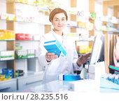 Купить «Pharmacist ready to assist in choosing at counter», фото № 28235516, снято 31 января 2017 г. (c) Яков Филимонов / Фотобанк Лори