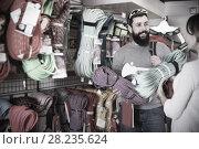 Купить «Positive man choosing alpinism cables in sports store», фото № 28235624, снято 24 февраля 2017 г. (c) Яков Филимонов / Фотобанк Лори