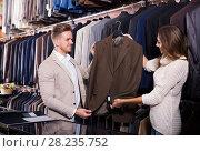 Купить «Happy couple examining various suits», фото № 28235752, снято 7 апреля 2020 г. (c) Яков Филимонов / Фотобанк Лори