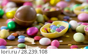Купить «chocolate easter eggs and drop candies on table», видеоролик № 28239108, снято 24 марта 2018 г. (c) Syda Productions / Фотобанк Лори