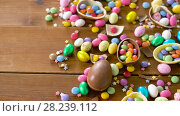 Купить «chocolate easter eggs and drop candies on table», видеоролик № 28239112, снято 24 марта 2018 г. (c) Syda Productions / Фотобанк Лори