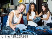 Купить «Girls choosing denim trousers together», фото № 28239988, снято 19 января 2019 г. (c) Яков Филимонов / Фотобанк Лори