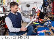 Купить «Man is choosing new wrench in tools store.», фото № 28245272, снято 9 января 2018 г. (c) Яков Филимонов / Фотобанк Лори