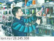 Купить «Man customer choosing fishing lures near stand in the sports shop», фото № 28245308, снято 16 января 2018 г. (c) Яков Филимонов / Фотобанк Лори