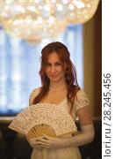 Купить «Attractive red haired woman in vintage 18 centuries dresses use fan in luxury ballroom», фото № 28245456, снято 30 марта 2018 г. (c) Константин Шишкин / Фотобанк Лори