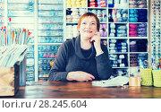 Купить «Positive saleswoman waiting for clients in store», фото № 28245604, снято 10 мая 2017 г. (c) Яков Филимонов / Фотобанк Лори
