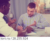 Купить «Two serious men analysing documents at home», фото № 28255924, снято 26 февраля 2018 г. (c) Яков Филимонов / Фотобанк Лори