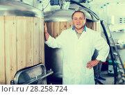 Купить «Adult brewer is standing near barrel for beer», фото № 28258724, снято 18 сентября 2017 г. (c) Яков Филимонов / Фотобанк Лори