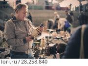 Купить «Man is visiting market of old things», фото № 28258840, снято 23 октября 2017 г. (c) Яков Филимонов / Фотобанк Лори