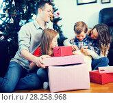 Купить «Positive family members presenting gifts on Christmas», фото № 28258968, снято 23 декабря 2016 г. (c) Яков Филимонов / Фотобанк Лори