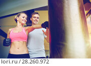 Купить «smiling woman with personal trainer boxing in gym», фото № 28260972, снято 29 июня 2014 г. (c) Syda Productions / Фотобанк Лори