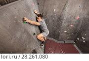 Купить «young man exercising at indoor climbing gym», фото № 28261080, снято 2 марта 2017 г. (c) Syda Productions / Фотобанк Лори