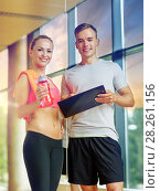 Купить «smiling young woman with personal trainer in gym», фото № 28261156, снято 29 июня 2014 г. (c) Syda Productions / Фотобанк Лори