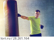 Купить «young man in gloves boxing with punching bag», фото № 28261164, снято 29 июня 2014 г. (c) Syda Productions / Фотобанк Лори