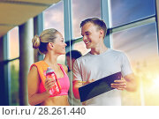 Купить «smiling young woman with personal trainer in gym», фото № 28261440, снято 29 июня 2014 г. (c) Syda Productions / Фотобанк Лори