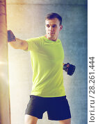 Купить «young man in gloves boxing with punching bag», фото № 28261444, снято 29 июня 2014 г. (c) Syda Productions / Фотобанк Лори