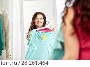 Купить «happy plus size woman with shirt at mirror», фото № 28261464, снято 21 февраля 2016 г. (c) Syda Productions / Фотобанк Лори