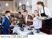 Купить «Polite smiling waitress bringing ordered dishes to guests at restaurant», фото № 28262208, снято 7 ноября 2017 г. (c) Яков Филимонов / Фотобанк Лори