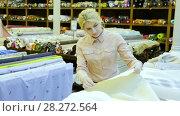 Купить «Young woman looking for interesting cloth in textile shop», видеоролик № 28272564, снято 28 марта 2018 г. (c) Яков Филимонов / Фотобанк Лори