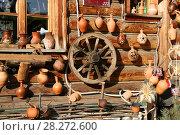 Купить «Керамическая посуда ручной работы, колесо от телеги на стене деревянного дома. Магазин сувениров, Москва, Измайловский кремль», эксклюзивное фото № 28272600, снято 25 марта 2018 г. (c) Щеголева Ольга / Фотобанк Лори