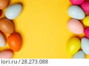 Купить «Colorful Easter eggs on a yellow background», фото № 28273088, снято 17 марта 2018 г. (c) Иван Карпов / Фотобанк Лори