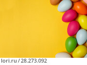 Купить «Colorful Easter eggs on a yellow background», фото № 28273092, снято 17 марта 2018 г. (c) Иван Карпов / Фотобанк Лори