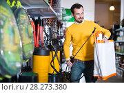 Купить «Smiling guy deciding on best garden sprayer», фото № 28273380, снято 2 марта 2017 г. (c) Яков Филимонов / Фотобанк Лори