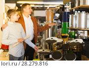 Купить «Father and teenage son examining drum units in guitar shop», фото № 28279816, снято 29 марта 2017 г. (c) Яков Филимонов / Фотобанк Лори