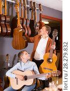 Купить «seller shows the best models of guitars», фото № 28279832, снято 29 марта 2017 г. (c) Яков Филимонов / Фотобанк Лори