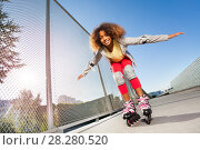 Купить «Active African girl rollerblading at skate park», фото № 28280520, снято 14 октября 2017 г. (c) Сергей Новиков / Фотобанк Лори