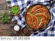 Купить «tasty fried sausages and green peas», фото № 28283664, снято 2 апреля 2018 г. (c) Oksana Zh / Фотобанк Лори