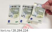 Купить «Купюра в десять евро кладется поверх трех купюр в пять евро, крупный план», видеоролик № 28284224, снято 26 февраля 2018 г. (c) Кекяляйнен Андрей / Фотобанк Лори