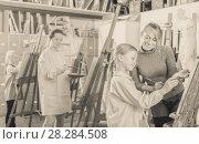 Купить «Female teacher assisting student during painting», фото № 28284508, снято 19 августа 2018 г. (c) Яков Филимонов / Фотобанк Лори