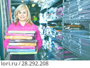 Купить «Portrait of mature woman showing stack of bedsheet in the textile shop», фото № 28292208, снято 17 января 2018 г. (c) Яков Филимонов / Фотобанк Лори
