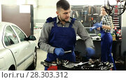 Купить «Man master is choosing instruments for work in workshop.», видеоролик № 28303312, снято 17 января 2018 г. (c) Яков Филимонов / Фотобанк Лори