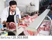 Купить «Man butcher weighing meat for client in shop», фото № 28303868, снято 15 сентября 2017 г. (c) Яков Филимонов / Фотобанк Лори