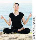 Купить «Smiling adult woman in black T-shirt is sitting and practicing asana», фото № 28304036, снято 15 мая 2017 г. (c) Яков Филимонов / Фотобанк Лори