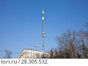 Купить «Вышка с антеннами и передатчиками на фоне синего неба в городе», фото № 28305532, снято 15 апреля 2018 г. (c) Victoria Demidova / Фотобанк Лори