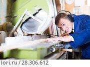 Купить «portrait of man in uniform working on electrical rotary saw indoors», фото № 28306612, снято 20 апреля 2018 г. (c) Яков Филимонов / Фотобанк Лори
