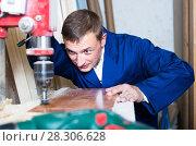 Купить «portrait of man in uniform working with electrical screwdriver on plywood indoors», фото № 28306628, снято 19 января 2019 г. (c) Яков Филимонов / Фотобанк Лори