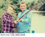 Купить «Smiling boy fishing with man on freshwater lake», фото № 28306644, снято 27 июня 2019 г. (c) Яков Филимонов / Фотобанк Лори