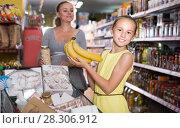 Купить «Smiling girl is showing chosen purchases», фото № 28306912, снято 5 июня 2017 г. (c) Яков Филимонов / Фотобанк Лори