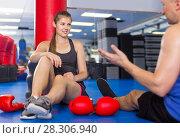 Купить «Female boxer is sitting with man and talking about healthy in gym.», фото № 28306940, снято 21 августа 2017 г. (c) Яков Филимонов / Фотобанк Лори