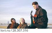 Купить «A few happy friends singing with the guitar at the sunset outdoors», видеоролик № 28307316, снято 24 апреля 2018 г. (c) Константин Шишкин / Фотобанк Лори