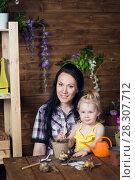 Купить «Mom and child are planting flowers», фото № 28307712, снято 14 апреля 2018 г. (c) Типляшина Евгения / Фотобанк Лори