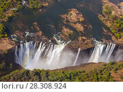 Купить «Victoria Falls, the largest curtain of water in the world. The falls and the surrounding area is the National Parks and World Heritage Site, Zambia and Zimbabwe.», фото № 28308924, снято 24 января 2019 г. (c) BE&W Photo / Фотобанк Лори