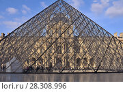 Купить «View fragments of Louvre buildings and pyramid in main courtyard (Cour Napoleon) of Louvre Museum. Louvre Museum is one of largest and most visited museums worldwide. France.», фото № 28308996, снято 16 января 2019 г. (c) BE&W Photo / Фотобанк Лори