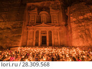 Large group of people sitting on the ground at night, the rock-cut architecture of Al Khazneh or The Treasury at Petra, Jordan. Стоковое фото, агентство BE&W Photo / Фотобанк Лори