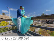 Купить «A young couple on their wedding day being photographed at the old Casearea harbor in Israel», фото № 28309620, снято 26 марта 2019 г. (c) BE&W Photo / Фотобанк Лори